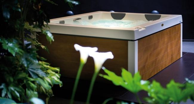 Jacuzzi® spa UNIQUE with TEAK panel in the garden